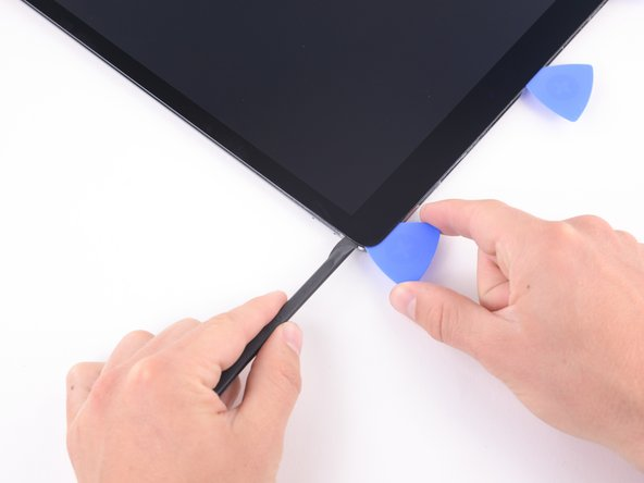 Bring the halberd spudger around the corner of the iPad and insert an opening pick in the upper right corner to prevent the adhesive from resettling.