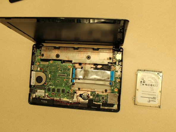 Gently remove the hard drive from the laptop by pulling it towards the right.