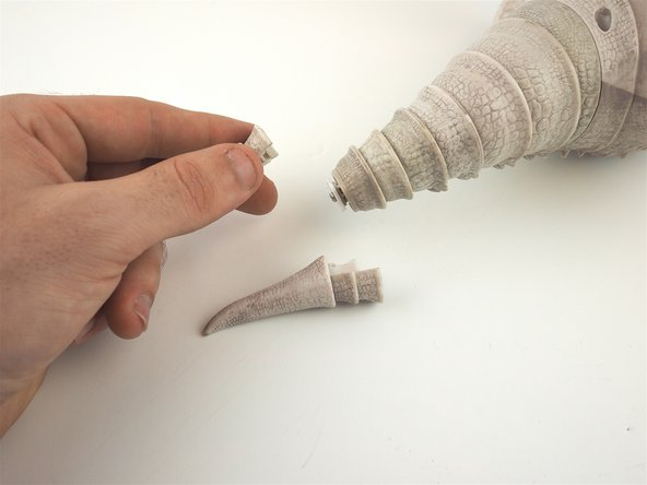 Use a spudger to pry apart the pieces of the tail, and gently remove the two pieces of the tip for replacement.