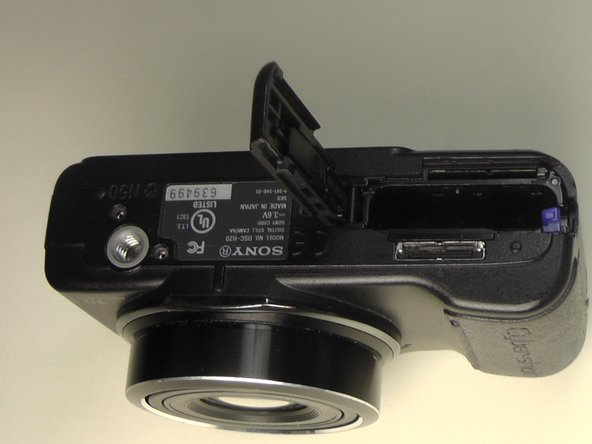 Place the camera upside down with the battery port positioned upward and the battery port open.