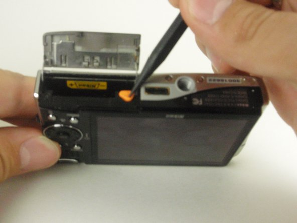 Push the orange release mechanism with the spudger in the direction of the arrow, freeing the battery.