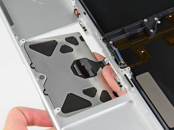 Insérez soigneusement la nappe de votre ancien trackpad à travers la fente découpée dans votre nouveau boîtier.