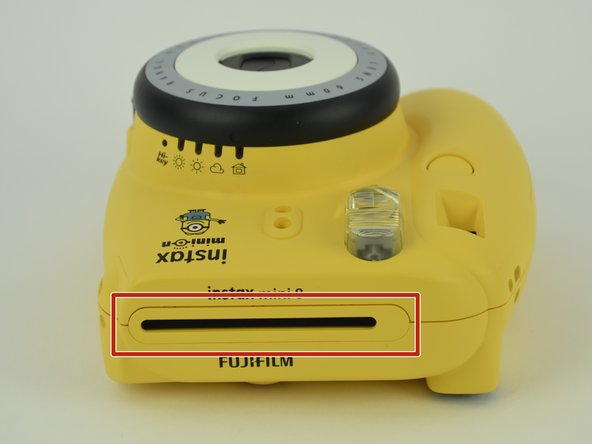 Use a spudger to remove the film slot guard on the top of the camera.