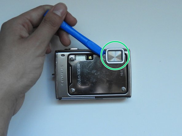 Using the spudger, pry off the plastic part of the lens.