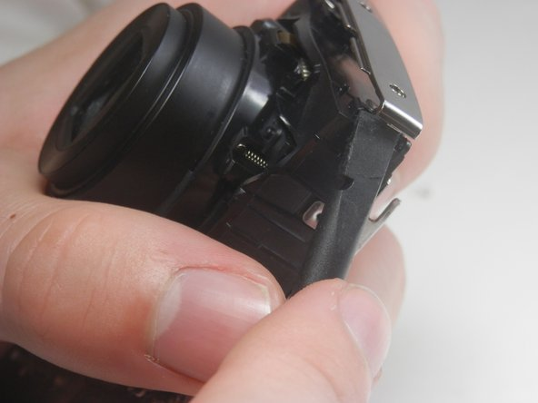 Pry the center casing off the camera. This is best done by separating the top and side sections individually.