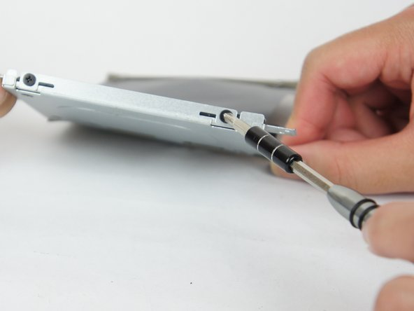 Using a JIS #0 screwdriver, unscrew the two 3.0 mm screws on the side of the metal casing to remove the hard drive itself.