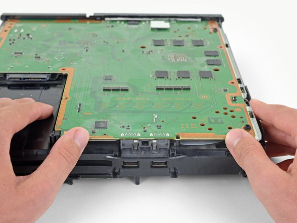 Grab the edge of the motherboard on the front of the PS4.