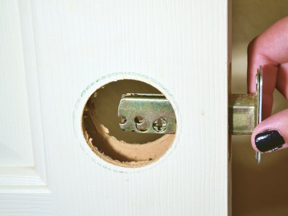 After all four screws have been taken out, slide the latch of the deadbolt out of the door frame.