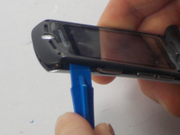 Use a plastic opening tool to pry the external shell off of the phone.