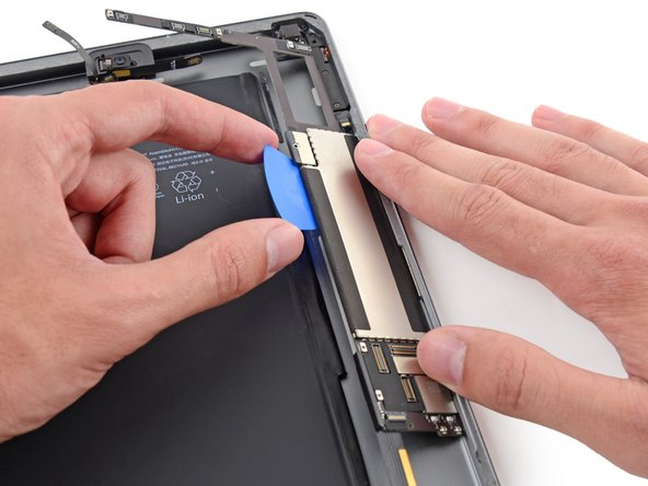 Image 3/3: Once the adhesive has been cut, pry the battery side of the logic board upward off of the rear case.
