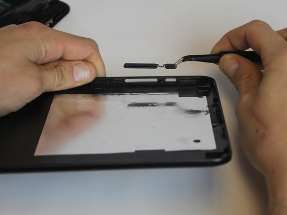 Carefully place the bottom lid next to the screen case. The power/speaker buttons should be visible at the corner of the lid. Remove the buttons with the tweezers.