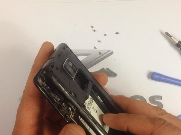 Use a plastic tool to remove the rear housing.