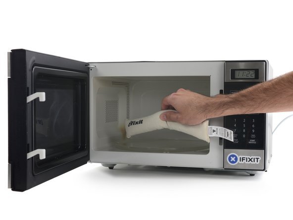 Image 1/3: Place the iOpener in the center of the microwave.