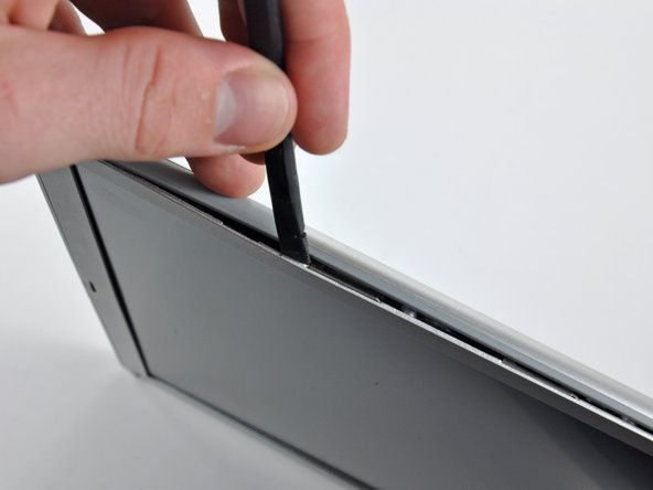 Rotate the tool away from the LCD to pop the rear bezel off the tabs on the front display bezel.