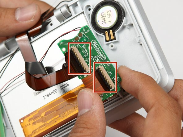 Move the black lock on the two large ribbon cables up with a pry tool, and gently pull out the two ribbon cables.