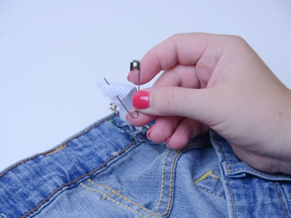 Using the safety pin, attach one end of the elastic strip to the waistband directly outside of one of the cuts.