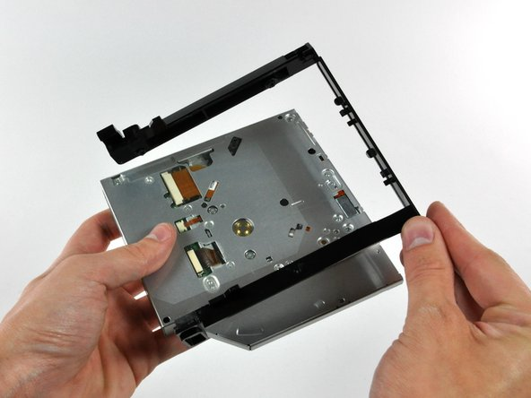 Pull the optical drive away from its bracket, minding any tabs that may still be caught in their slots.