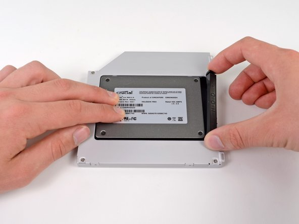 Image 1/2: Once the hard drive is snug, reinsert the plastic spacer while holding the hard drive against the bottom of the enclosure.