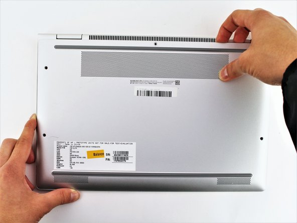 Separate the bottom cover from the laptop, starting from the upper corner and working your way around the edge.