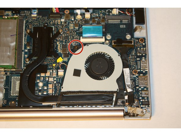 Remove the screw attaching the cooling fan to the motherboard by using a PH-1 screwdriver.