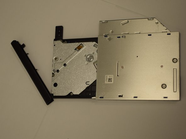 Gently pry the bezel from the face of the optical drive.