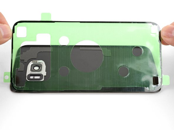 Hold the exposed strip by its tabs and carefully line up a long edge of the adhesive to the edge of the back cover.