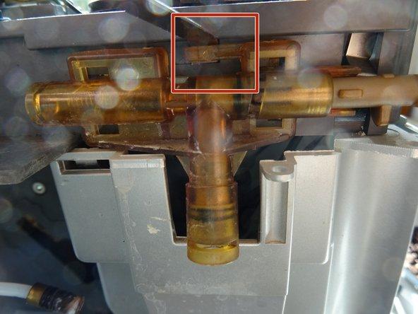 Das Dampfventil ist noch mit einer Raste gesichert. Hebe die Raste mit einem Flachschraubendreher an und schiebe das ganze Ventil nach rechts.