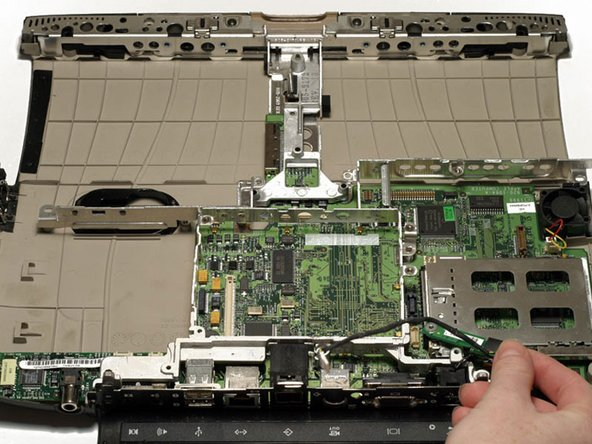 Grasp the EMI Filter by its black end and rotate it toward the front of the laptop. Pull the filter up and beyond the screw bracket.