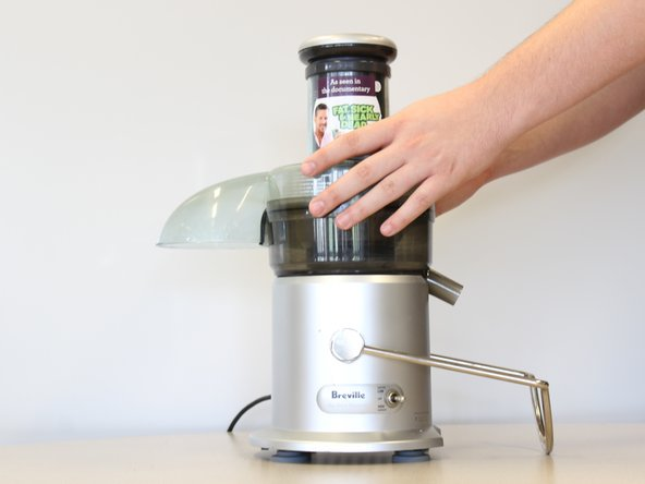 Firmly grip both sides of the juicer. Twist clock-wise and lift to remove the lid.
