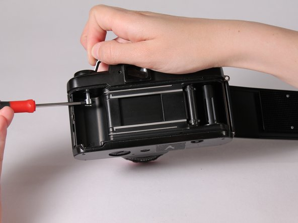 With one hand holding the screwdriver in the notch, wind the crank counter-clockwise to remove it.
