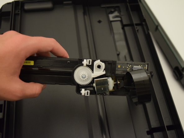 Lift the scanning piece and detach the  ribbon cable by gently pulling on it.