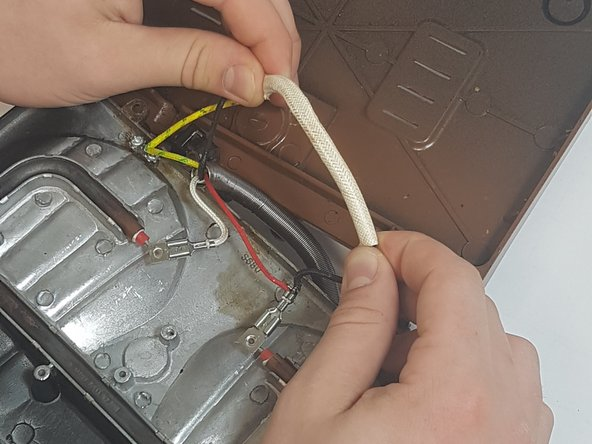 Move the rope-like sleeve to the left side to reach the thermal fuse.