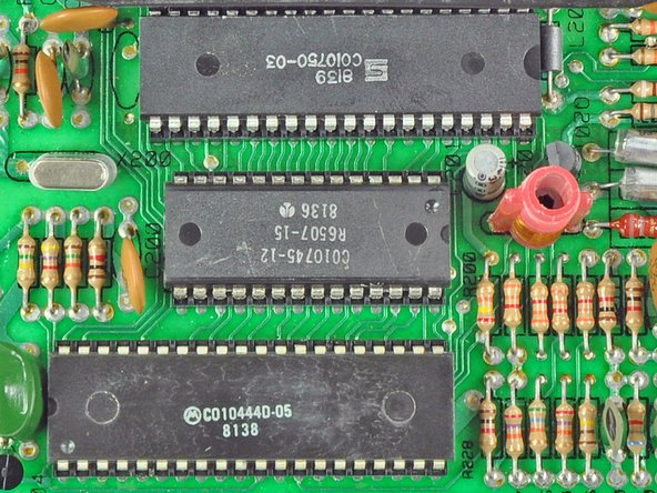 The top two chips are the 6532 Ram-I/O-Timer (RIOT) chip and MOS Technology's 6507 CPU (a slimmer version of the more popular 6502). By the current revision, they were manufactured by Synertek and Rockwell, respectively.