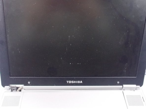 Locate the two screw covers and screws that can be found underneath the screen of the laptop.