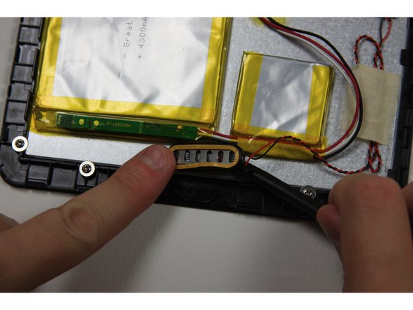 Using the flat end of the spudger, remove the speaker from the device by sliding the spudger underneath the speaker.