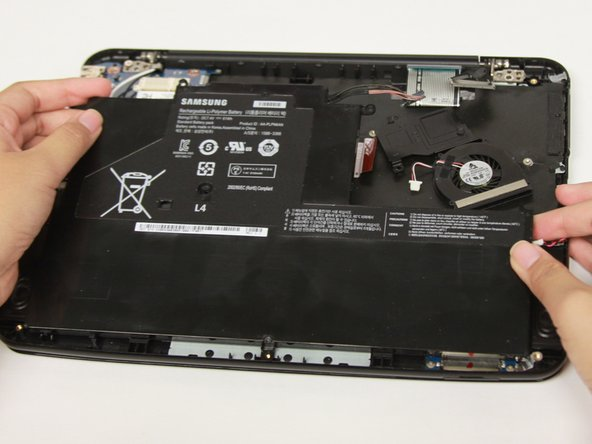 Carefully lift the top of the battery then pull it away from you to remove it.