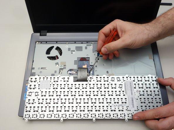Libérez maintenant en vous aidant d'un tourne-vis le câble du clavier à droite.