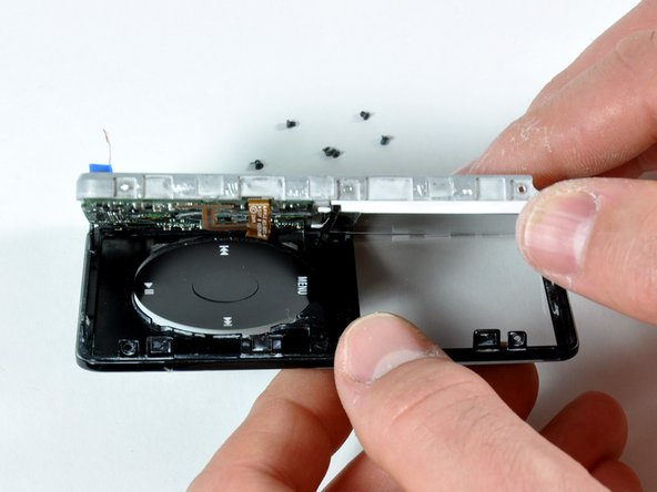 Carefully work around the edge of the iPod to separate the front panel from the metal framework.