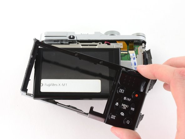 Slide the frame around the LCD to remove it from the camera.