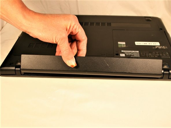 From the underside of the laptop, press the two battery tabs inward to remove the battery.  Lift the battery to remove.