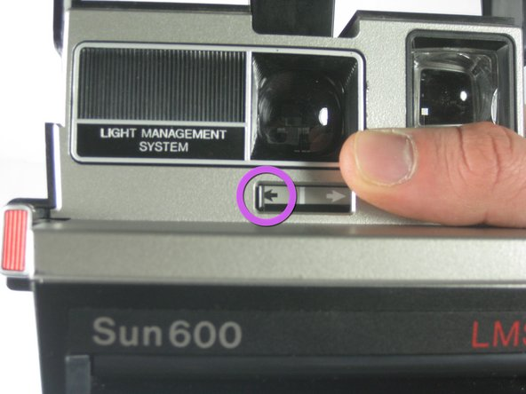 Slide light switch towards the black arrow on the left to decrease exposure.