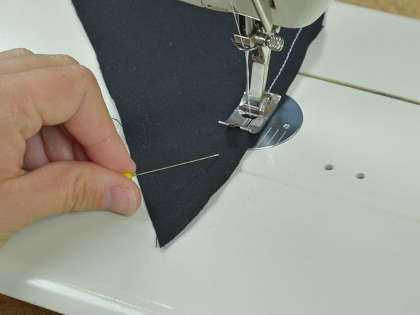 Pull out the last pin and sew up to the fabric's end.