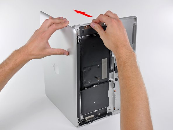 Image 1/3: Grab the upper case with your right hand and rotate it slightly toward the top of the display so the upper display bracket clears the edge of the upper case.