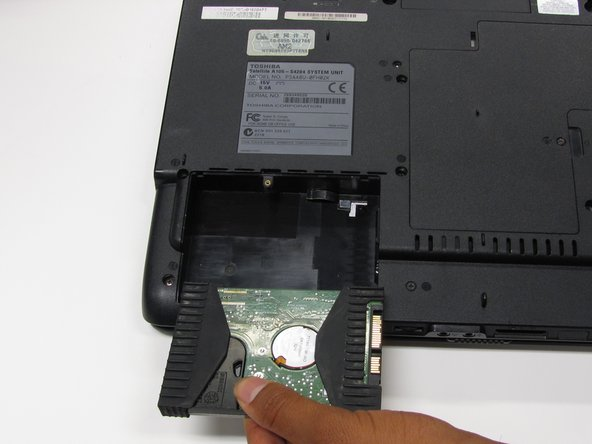 Pick up the near side of the hard drive and pull it out the back.