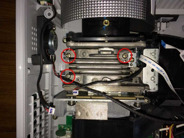 Remove 3 screws on the top of the optical assembly. On the right, do not remove the adjacent screw securing the colour wheel assembly.