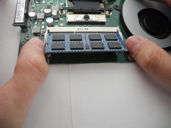 Image 3/3: When reassembling, slide RAM in as far you can at a 45 degree angle and snap it down into place.