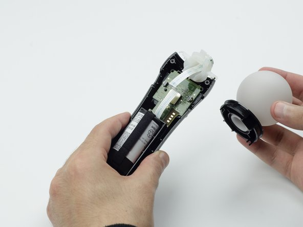 Hold the base of the controller with one hand and with the other carefully pull up on the white spherical piece to remove it.