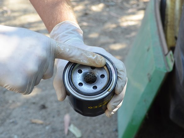 Dip a clean, gloved finger into a fresh bottle of oil and spread a thin layer of oil on the new oil filter's gasket.