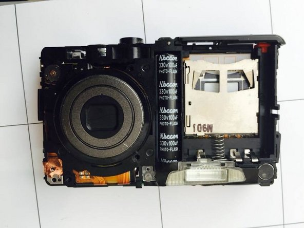 This is what the camera should look like with all screws are removed. Flip camera over to carefully remove the screen cover.