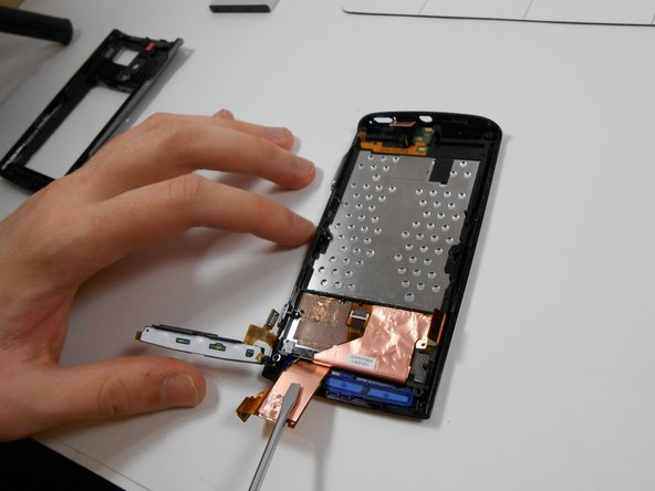 Using a flat head screw driver, disconnect the glue holding the left ribbon cable to the phone. Once unglued, the cable should flip back and still be connected to the phone. Pull up the black plastic piece being pointed to in the image.